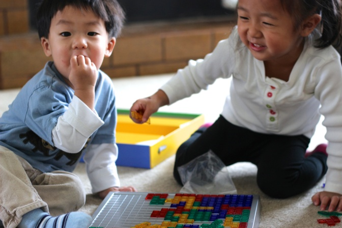 Laughing at Noah eating the Blokus instead of playing with it.