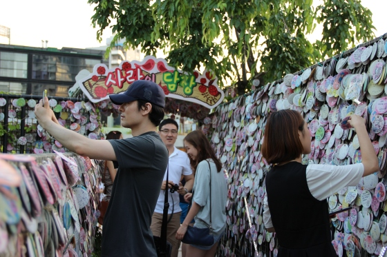 Self-pic time! Maybe to tell his girl that he misses her at this Love Wall. Or maybe for his online dating profile.