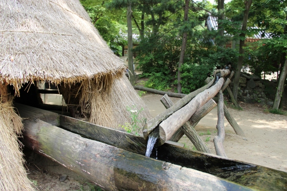 Simple water mill. The weight of the water lifts the sledgehammer until the water tips out and releases it.